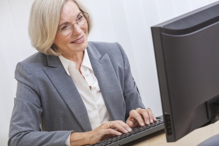 Senior woman typing using a computer at home or in an office photo