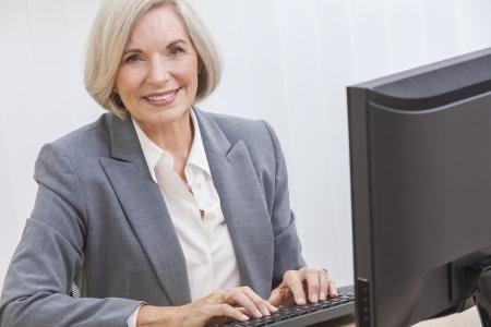 Senior vrouw te typen met behulp van een computer thuis of op kantoor