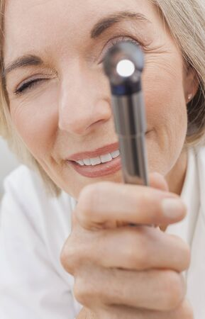 speculum: Close up of senior woman female medical hospital doctor using an otoscope or ear speculum to examine a patient