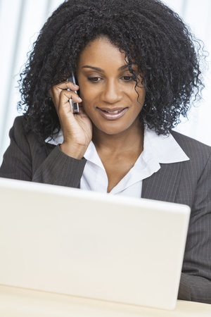 Portrait of a beautiful middle aged African American woman or businesswoman smiling using a cell phone and laptop computer Stock Photo - 19423448