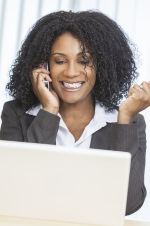business woman phone: Portrait of a beautiful middle aged African American woman or businesswoman smiling using a cell phone and laptop computer