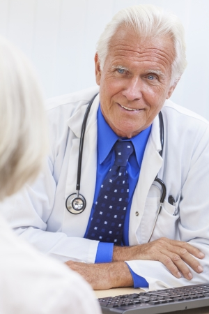 A senior male doctor sitting at a desk in an office with a computer, wearing a shirt, tie and stethoscope talking to elderly female patient photo