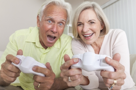 sexes: Senior couple, man and woman, laughing & having fun playing video console games together.