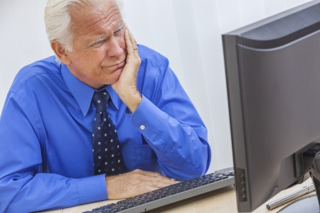 computer problem: A senior man male sitting at a desk wearing a shirt & tie having trouble or problems using a computer Stock Photo