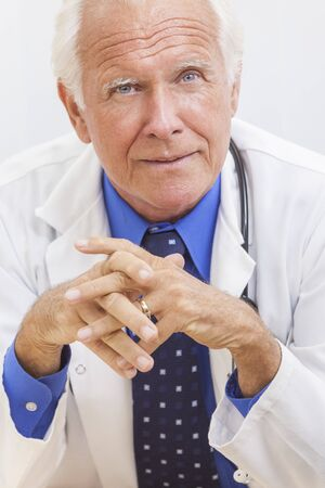 consultant physicians: A senior man male medical hospital doctor sitting at a desk wearing a shirt, tie and stethoscope