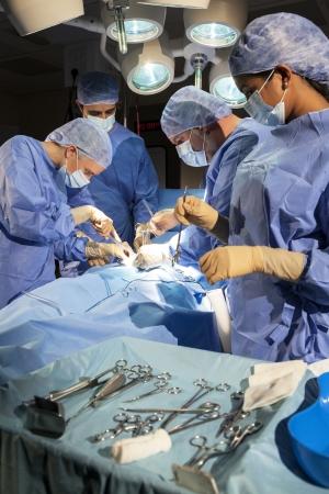 quirurgico: Un equipo de m?dicos interraciales macho y hembra los cirujanos en la cirug?a de operaci?n en un paciente utilizando diferentes instrumentos de equipo m?dico vistiendo batas y m?scaras Foto de archivo