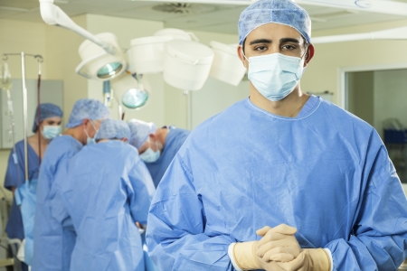 surgeon operating: Indian Asian male surgeon and his team of interracial male & female surgical medical doctors in hospital operating theater performing surgery on a patient wearing scrubs and masks