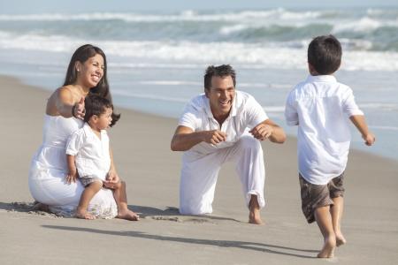 Een gelukkige Spaanse familie van moeder, vader en twee kinderen, jongen zonen, spelen en plezier in het zand van een zonnig strand