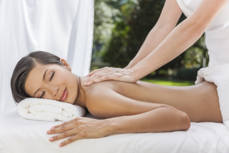 oriental massage: An Asian Chinese woman relaxing outside at a health spa while having a massage treatment Stock Photo