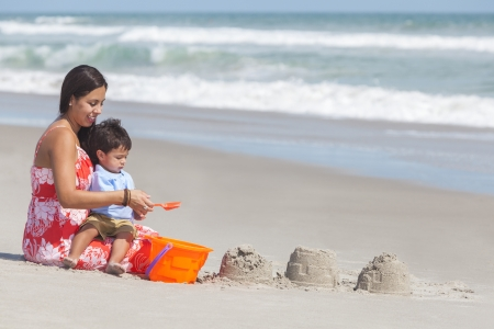 A happy hispanic mother and young child boy son having fun in the sand together making sand castles on a sunny beach Banco de Imagens