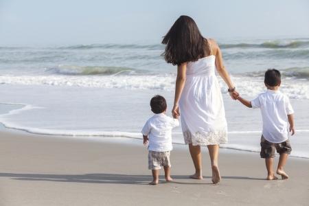 mujer hijos: Una familia feliz de madre hispana única, y dos niños hijos niños, caminando de la mano en el mar y la arena de una playa soleada