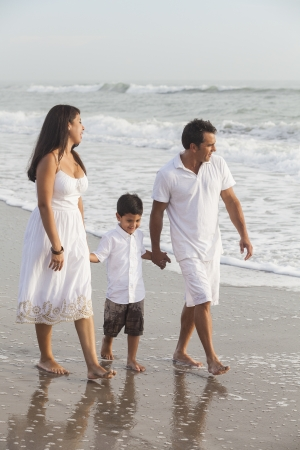 A happy family of mother, father and child, boy sons, holding hands & walking in the sand of a beach