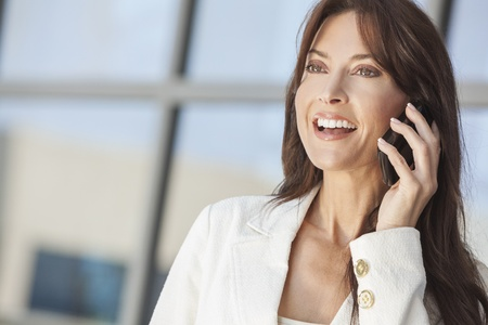 beautiful middle aged woman: Outdoor portrait of a beautiful happy brunette woman or businesswoman in her thirties talking on her cell phone