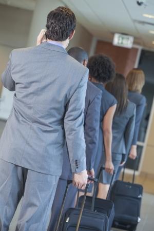 file d attente: Groupe ou d'une équipe d'hommes et de femmes, d'hommes d'affaires et femmes d'affaires parlant au téléphone cellulaire et les voyages en ligne dans un aéroport avec des valises de roulement