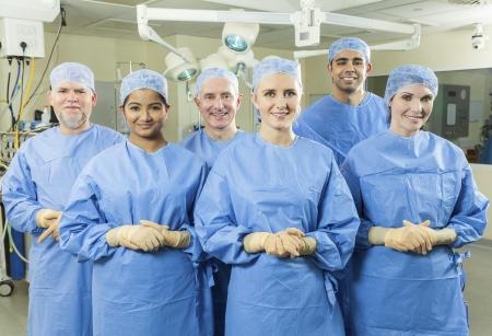 Een medisch team van interraciale artsen mannen en vrouwen chirurgen in een ziekenhuis operatiekamer dragen schrobt en chirurgische handschoenen op zoek gelukkig en succesvol