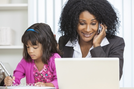 single parent: Beautiful middle aged African American woman or businesswoman working on her cell phone & laptop computer and looking after her female child daughter