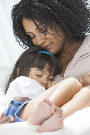 Portrait of a beautiful middle aged African American woman at home eyes closed relaxing sleeping loving hugging her female child daughter