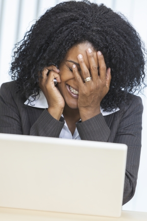 Middle aged African American woman or businesswoman suffering stress with problem on cell phone & laptop computer Stock Photo - 19445771