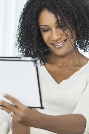 Beautiful smiling African American woman using her tablet computer. Stock Photo - 19445724