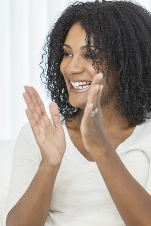 Portrait of a beautiful middle aged African American woman sitting at home relaxing laughing & clapping Stock Photo - 19445727