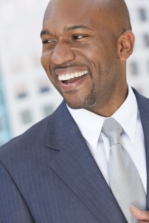Happy smiling successful African American businessman or man in a suit in a modern city  photo