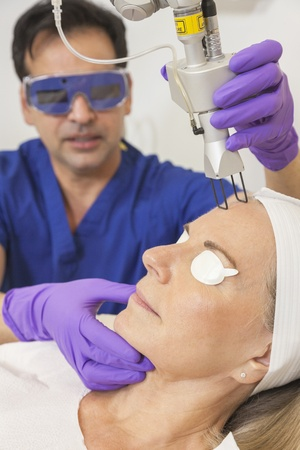 A cosmetic surgeon doctor giving fractional CO2 laser skin treatment to the face of a senior female woman patient Banco de Imagens