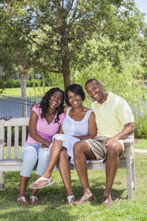 A happy black African American family of two parents and one female girl child sitting together outside on a park bench laughing.