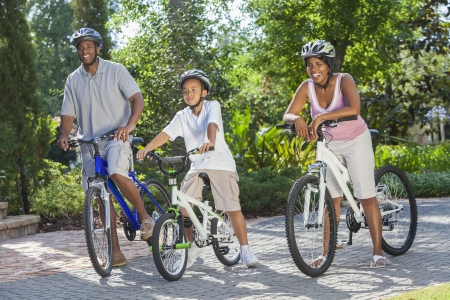 happy black family: A young African American family, woman, man, father, mother & boy child riding bicycles in the summer Stock Photo
