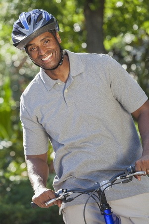 middle aged: An African American man riding bicycle in the summer Stock Photo