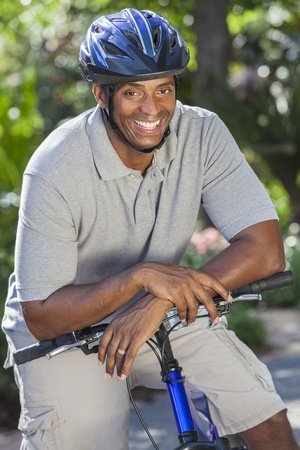 An African American man riding bicycle in the summer photo