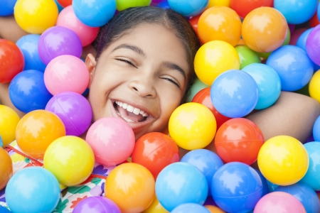 hundreds: Happy African American girl child laughing & playing in hundreds of colorful plastic multi-colored balls