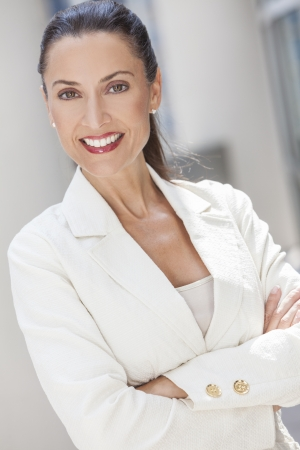 Outdoor portrait of a beautiful smart brunette woman or businesswoman in her thirties wearing a suit
