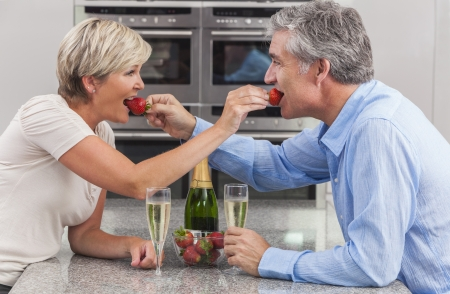 An attractive happy, smiling, romantic man and woman couple sharing strawberries and champagne in a kitchen photo