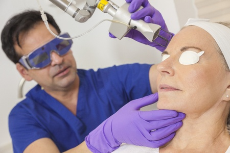 skin treatment: A cosmetic surgeon doctor giving fractional CO2 laser skin treatment to the face of a senior female woman patient Stock Photo