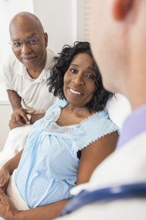 Happy senior African American woman patient recovering in hospital bed with male doctor and husband