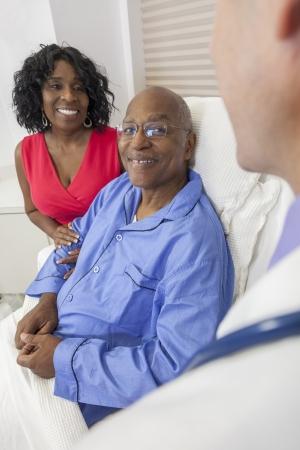 paciente: Feliz hombre paciente afroamericano alto recuper�ndose en cama de hospital con el doctor de sexo masculino y mujer