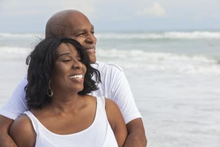 Gelukkig romantische senior Afro-Amerikaanse man en vrouw paar op een verlaten tropisch strand