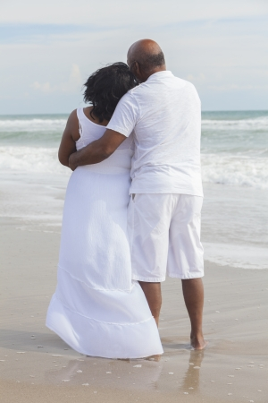 Rear view of senior African American man and woman couple on a deserted tropical beach  photo