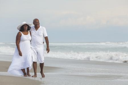 parejas caminando: Feliz el hombre rom�ntico senior de afroamericano y joven mujer en una playa tropical desierta