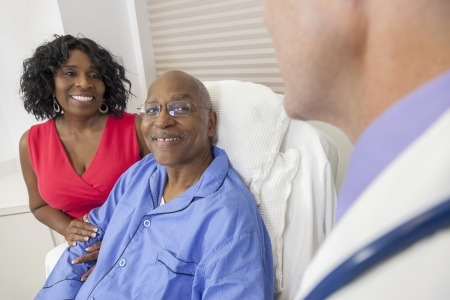 Gelukkig senior Afro-Amerikaanse man patiënt herstelt in het ziekenhuis bed met mannelijke arts en vrouw Stockfoto