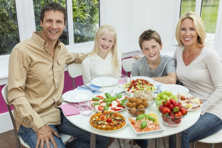 An attractive happy, smiling family of mother, father, son and daughter eating healthy salad at a dining table  photo