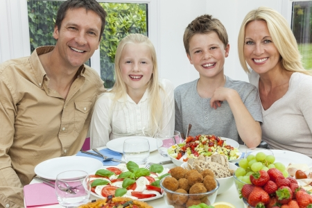 An attractive happy, smiling family of mother, father, son and daughter eating healthy salad at a dining table Stock Photo - 19483558
