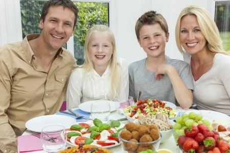 familia comiendo: Un atractivo familia feliz y sonriente de la madre, padre, hijo y su hija comiendo ensalada saludable en una mesa de comedor Foto de archivo