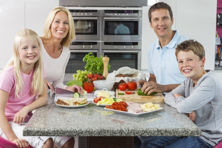 An attractive happy, smiling family of mother, father, son and daughter preparing and eating healthy food in kitchen at home photo