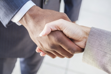 mãos: Empresário africano americano homem ou apertar as mãos de uma mulher de negócios ou uma mulher caucasiano colega fazendo um negócio