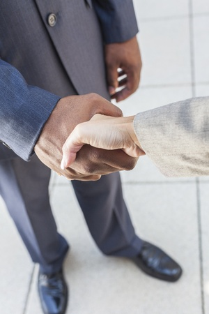 African American businessman or man shaking hands with a businesswoman or woman caucasian female colleague making a business deal photo