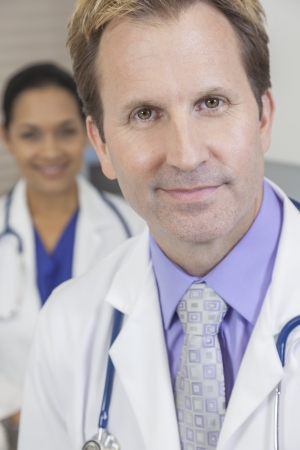 consultant physicians: A male doctor wearing a shirt, tie and stethoscope with female Latina colleague behind him