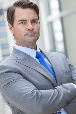 Successful smart businessman or man serious and thinking with arms folded in a suit in a modern city Stock Photo - 19483547