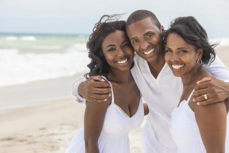 Een gelukkig lachend lachende Afro-Amerikaanse familie van vader moeder en dochter op het strand in de zomer