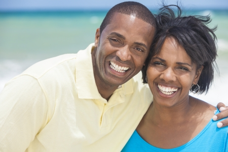 smile teeth: A happy smiling laughing African American man and woman couple at the beach in the summer
